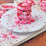 pink decorated cookies sitting on plate