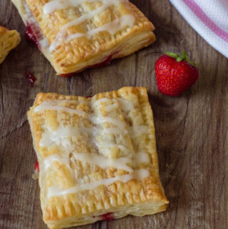 Puff Pastry Strawberry Strudel on a table with strawberries next to it