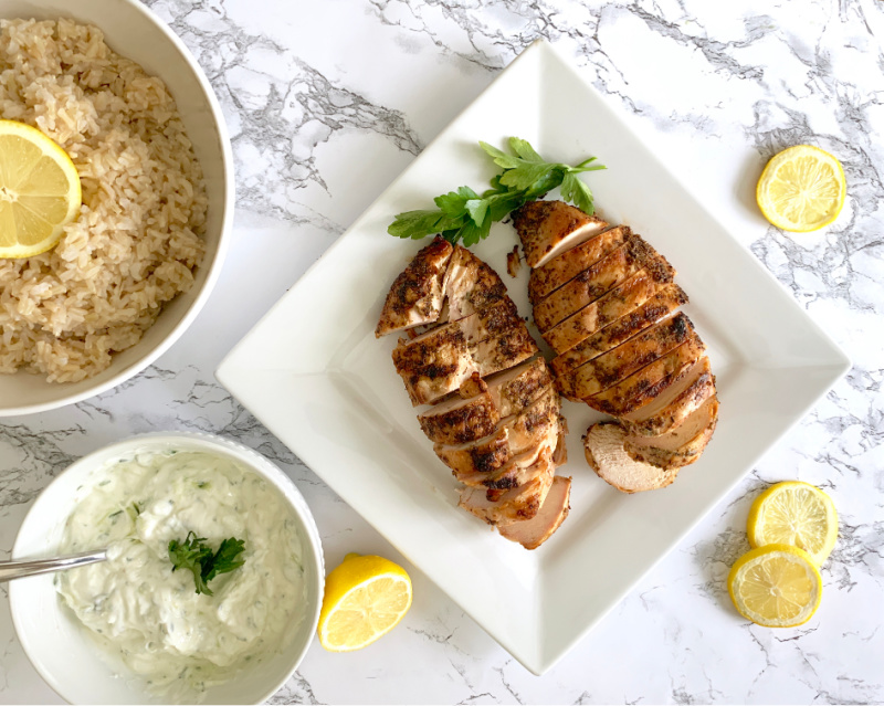 Chicken on a plate with rice near by