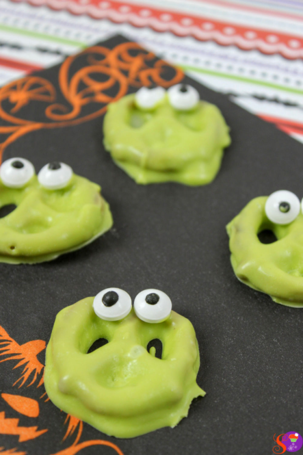 Pretzels are dipped into bright green melted chocolate, then candy eyes are added for a silly monster look in this no-bake Halloween Monster Pretzel recipe  the whole family will enjoy!
